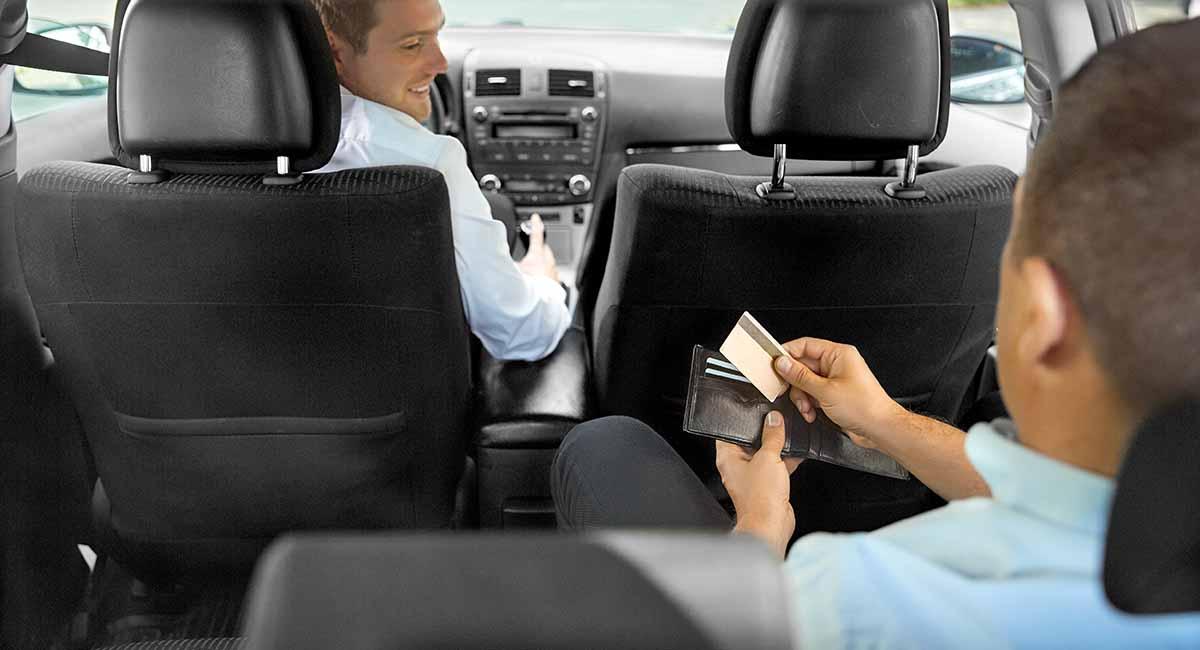 Passageiro pagando com cartão no táxi