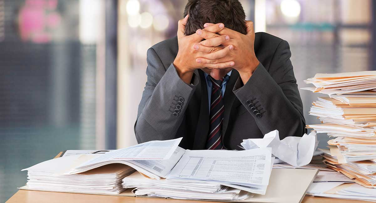 Homem olhando para papelada necessária para aluguel de máquina de cartão