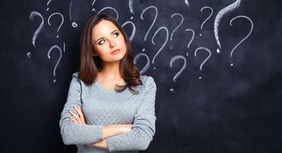 Mulher olhando para interrogações