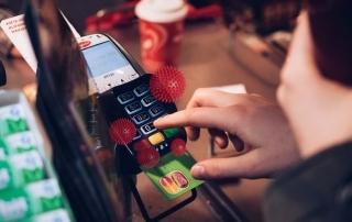 Homem digitando em máquina de cartão com símbolos representando o coronavírus