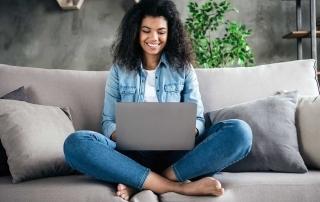 Mulher sentada no sofá criando loja virtual no laptop