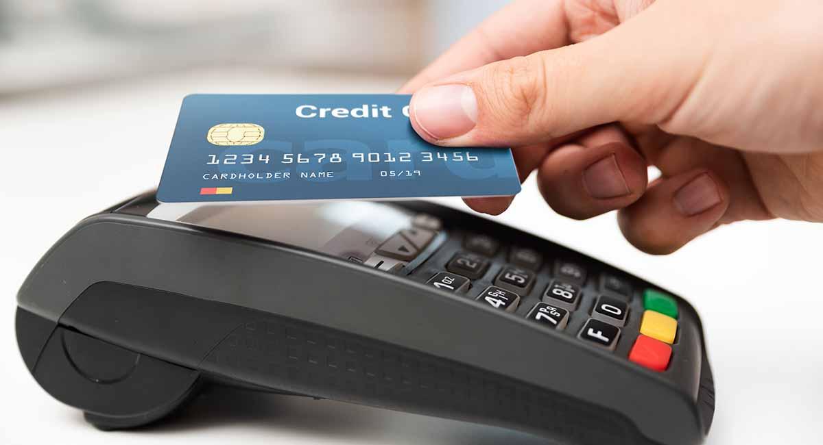 Mão aproximando cartão de máquina para pagar via NFC