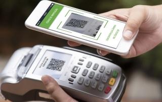 Máquina de cartão e celular realizando pagamento com QR Code