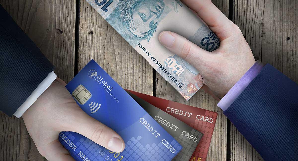 Mão entregando dinheiro e outra entregando cartão de crédito em autorização parcial de pagamento