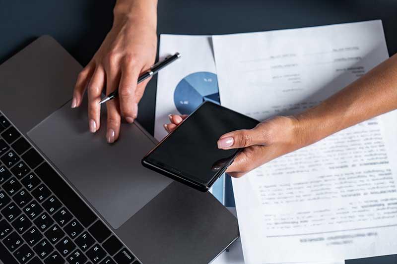 Pessoa com celular e notebook lidando com documentação