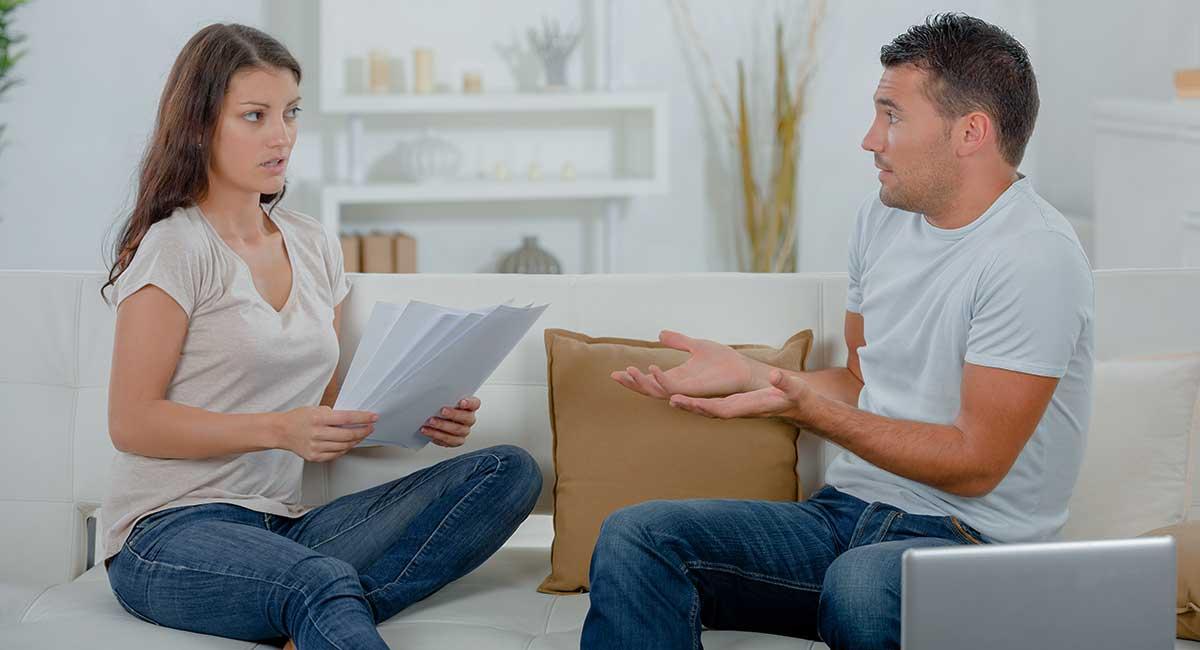 Mulher com papéis na mão falndo com outro homem no sofá