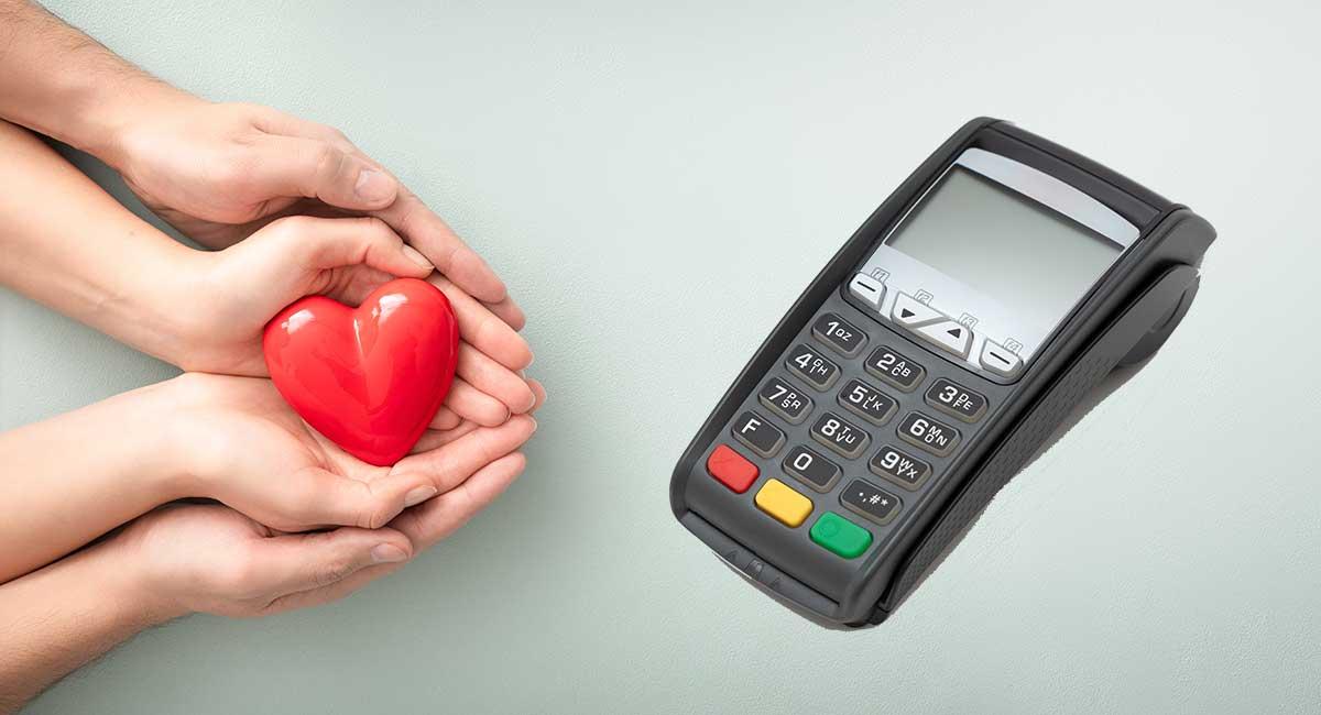 Mãos oferecendo coração ao lado de máquina de cartão
