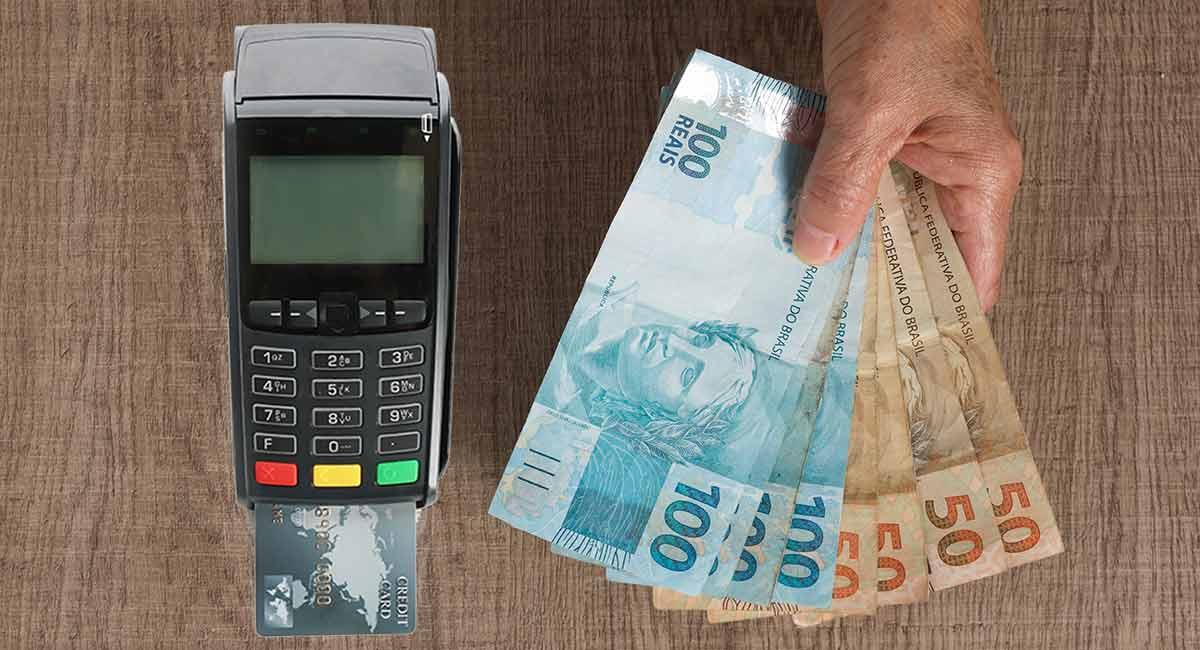 Máquina de cartão ao lado de dinheiro de empréstimo