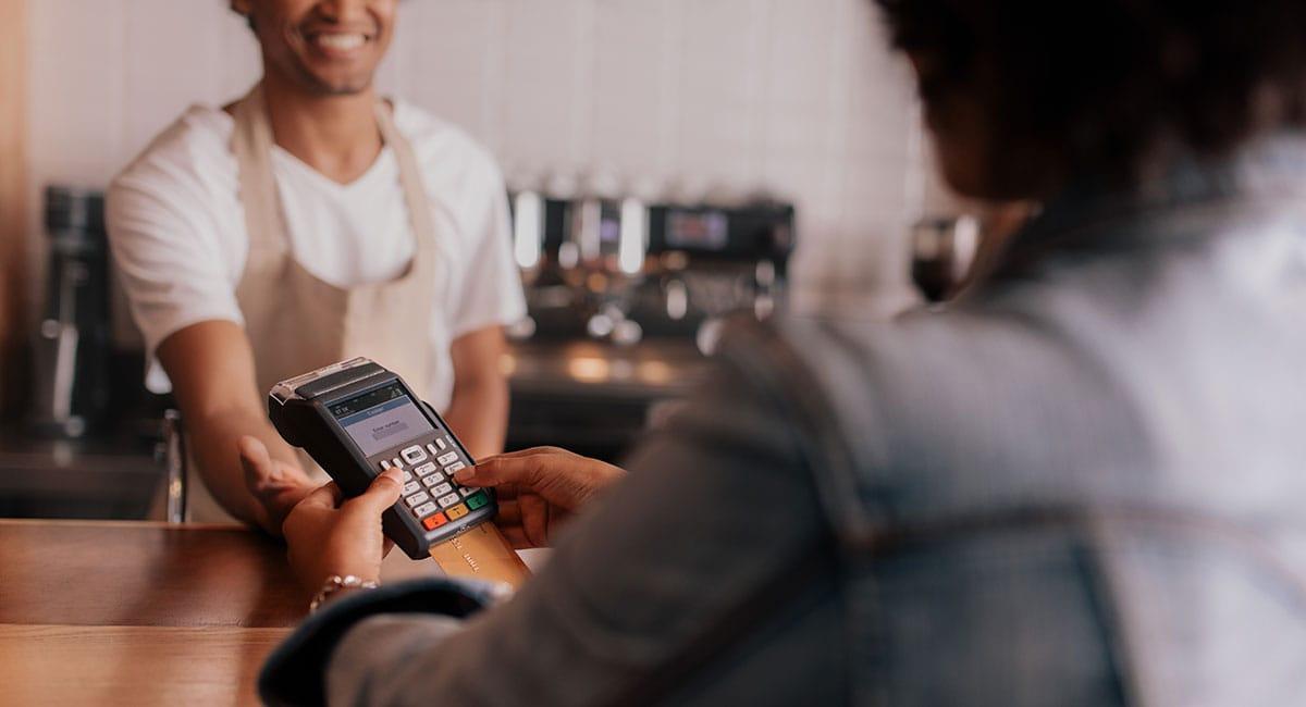 cliente digitando senha na máquina de cartão em frete ao vendedor
