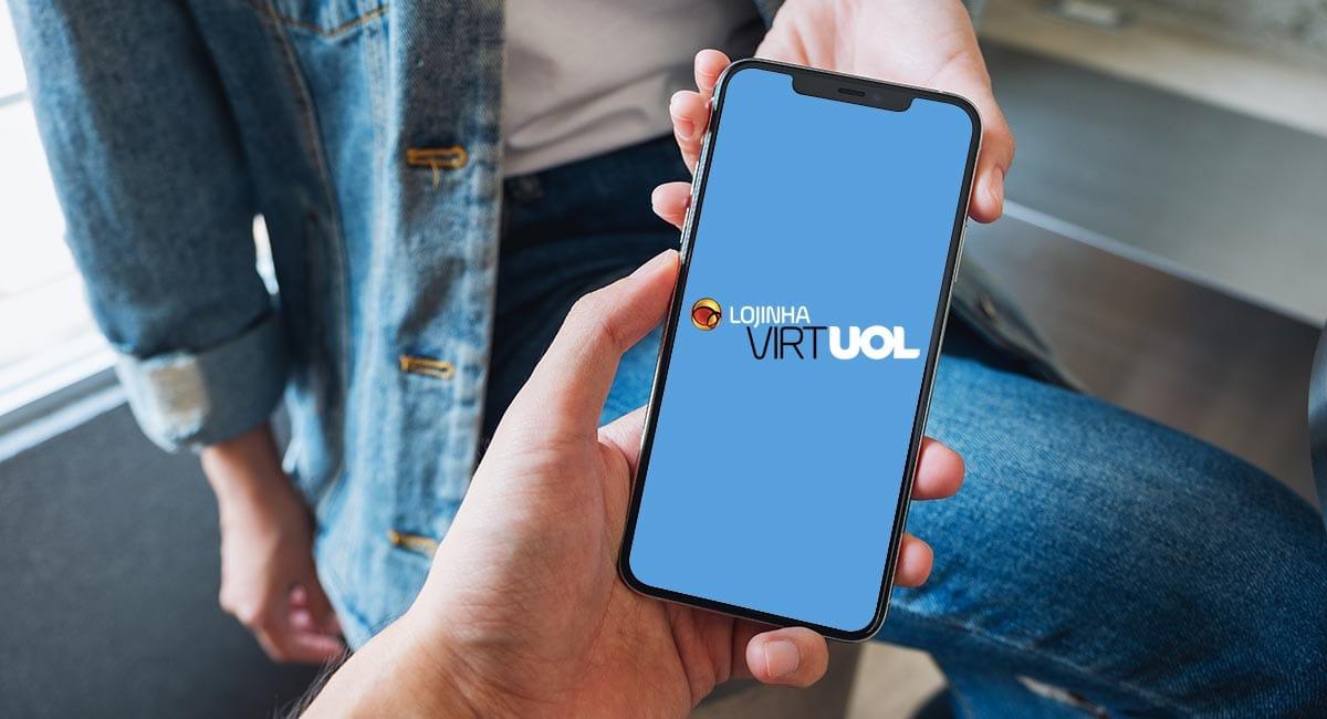 Mão segurando celular com logo da Lojinha Virtual Uol