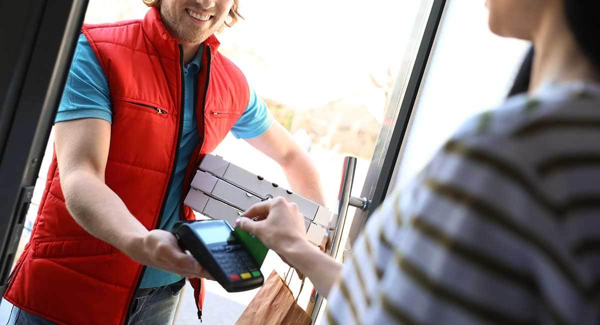 Entregador recebendo pagamento na entrega de pizza