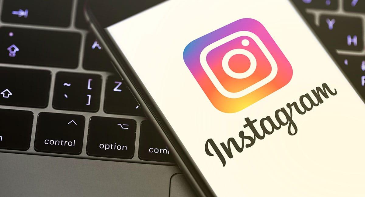 Logo Instagram em celular em frente ao laptop