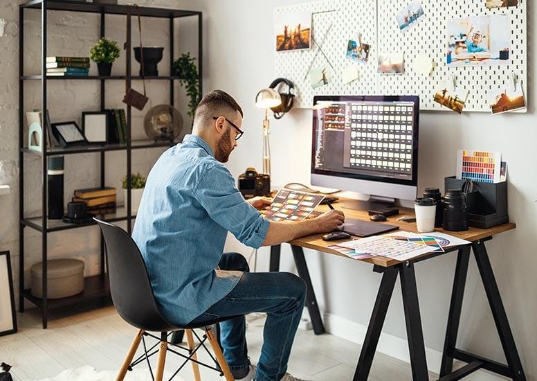 Homem sentado em frente `amesa do computador ao lado de armário