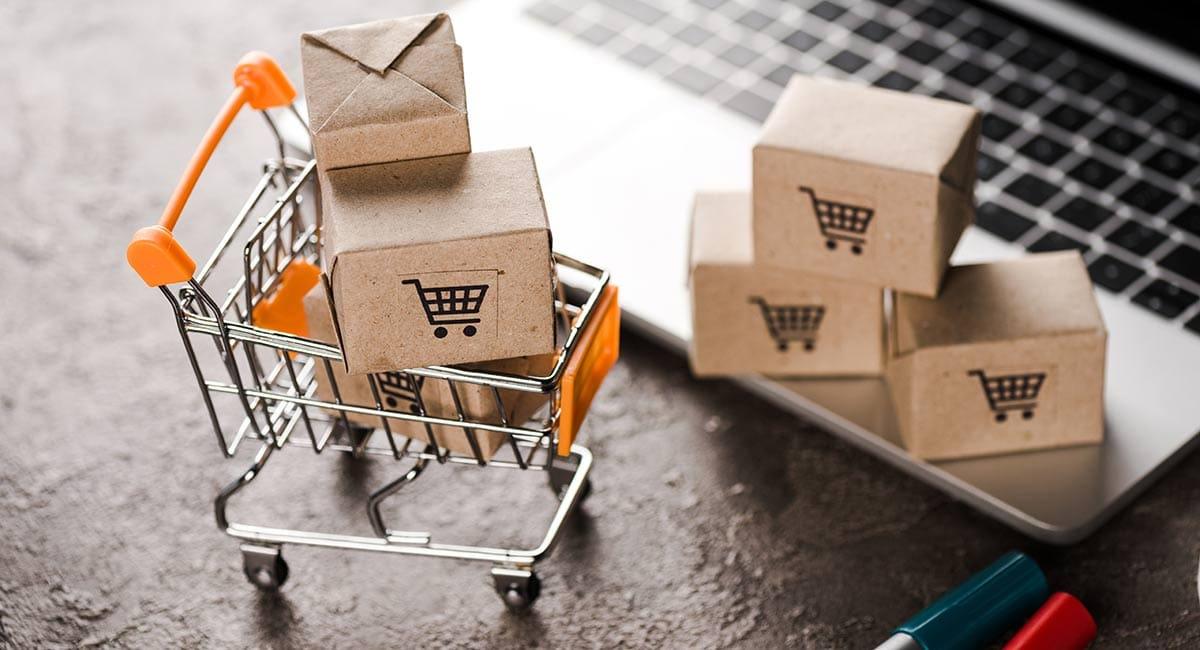 carrinho de compras com caixas em frente a um laptop