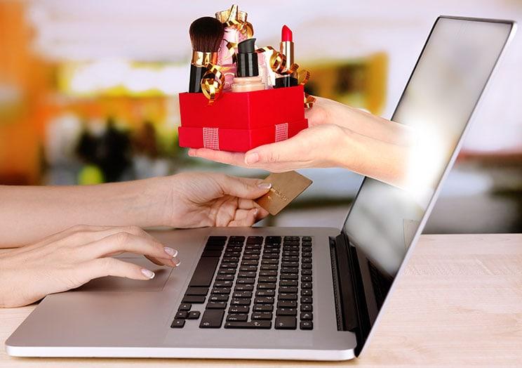 Mão saindo do laptop entrega perfumes e cosméticos para mão com cartão