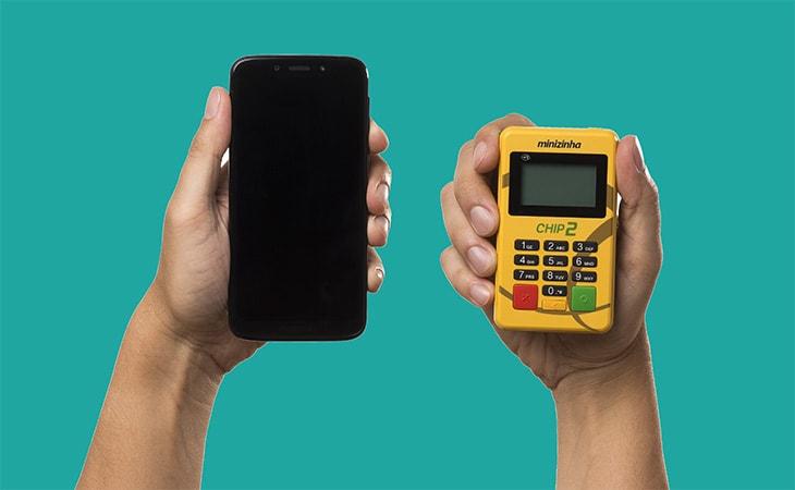 Mãos segurando Minizinha Chip 2 e celular