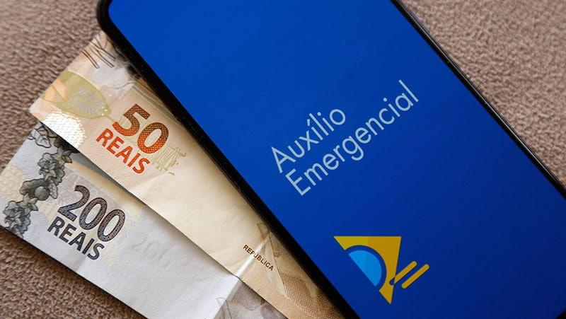 Logo do Auxílio Emergencial na tela de celular ao lado de cédulas de reais