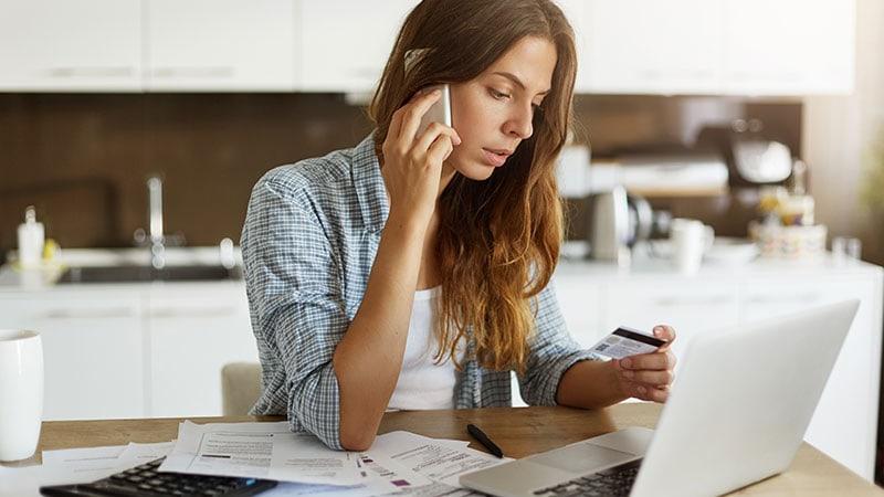 Mulher falando no celular com cartão na mão