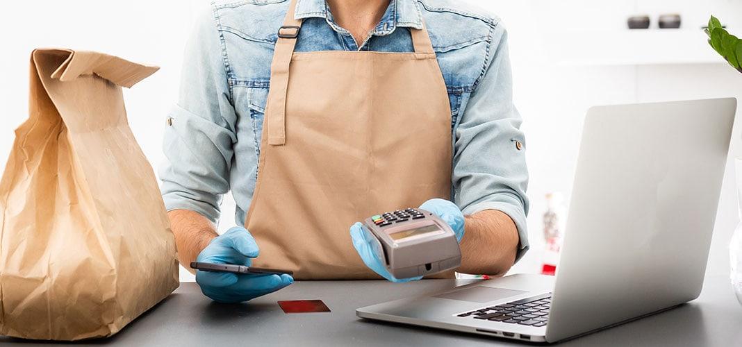 Vendedor com pacote para entrega, maquininha de cartão e notebook