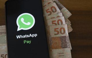 Celular com logo WhatsApp Pay e cédulas de reais