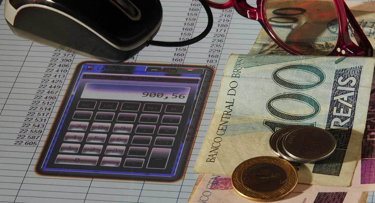 Calculadora e dinheiro paa cálculo de taxa de antecipação